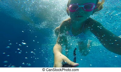 Underwater happy beautiful girl in swimming pool having fun