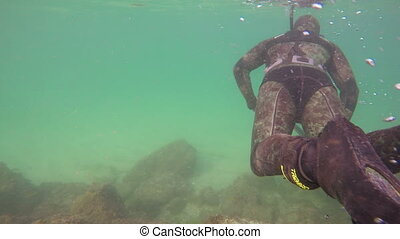 Underwater hunter gets a gun at the bottom, and swims on a fishing trip.
