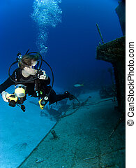 Underwater Photographer looking at a Sunken Ship with...