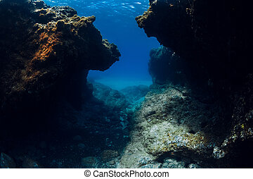Underwater scene with rocks in blue sea