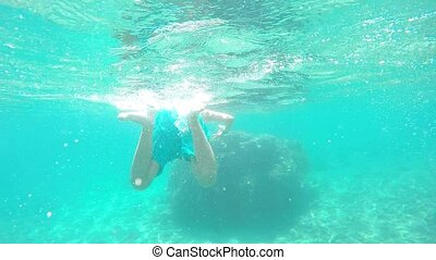 underwater shot of a cute little boy snorkeling with a mask...