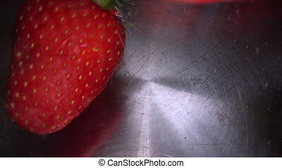 Underwater shot of fresh strawberries being dropped into the...