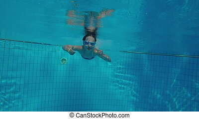 Underwater video of a girl jumping in swimming pool