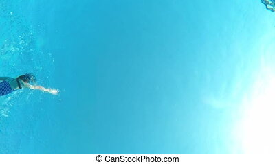Underwater view of a girl swimming in pool - Underwater view...