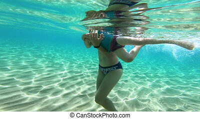 Underwater view of a mother holding her baby daughter and learning to swim in the sea water