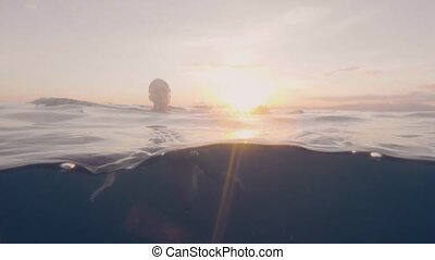 Underwater view young woman swimming in blue sea and golden...