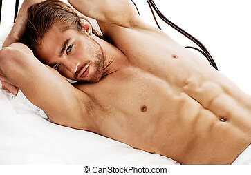 undress - Handsome nude man lying in a bed. Isolated over...