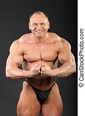 Undressed bronzed smiling bodybuilder demonstrates his arm muscles