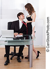 Undressed Businesswoman Pulling Boss Towards Self In Office...