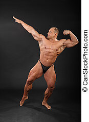 Undressed tanned bodybuilder aiming for punch in black studio
