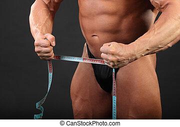 Undressed tanned bodybuilder holds measuring tape in black studio