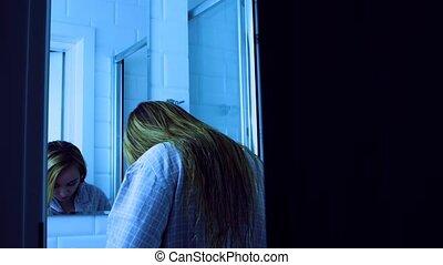 Peeping woman while underssing behind door ajar in bathroom. Privacy problem.
