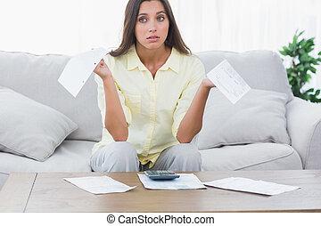 Uneasy woman doing her accounts