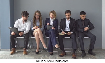 Unemployed expect interviews sitting on chairs in the hallway of an office building.