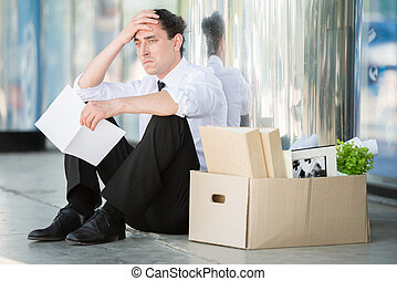 Fired frustrated man in suit sitting near office.