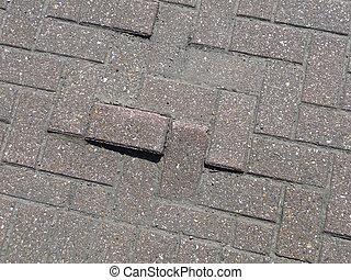 Some uneven bricks on the ground.