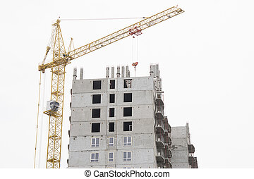 Unfinished house with a crane on construction site