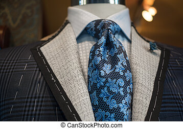 Close-up of an unfinished checkered jacket with white thread stitches and blue patterned tie.