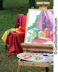 unfinished painting on the easel with colorful palette