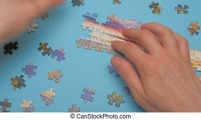 Closeup hands connecting jigsaw puzzle on blue background. Man's hands arranging jigsaw puzzle. Business solutions, success and strategy concept. Hobby and leisure activity indoor. Brain training
