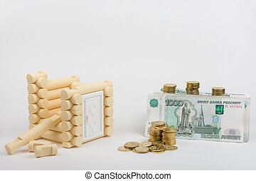 Unfinished toy house, next are Russian rubles banknotes and coins