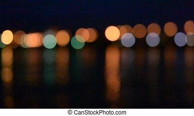 Unfocused city and traffic lights at night near water