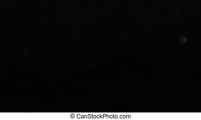 Unfocused grey flying circles on a black background HD