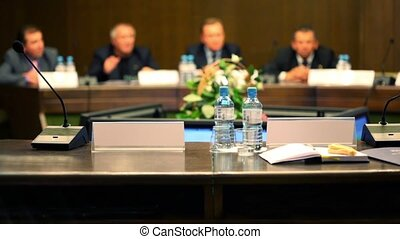 Unfocused men in business suit sit at the table on conference