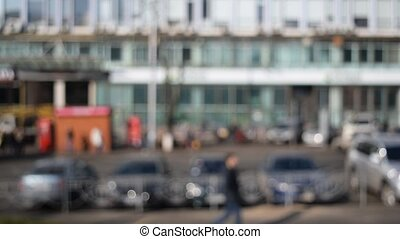 Unfocused view of a city with people and cars passing by