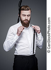 Unforeseen fail. Frustrated young bearded man adjusting his suspenders and keeping eyes closed while standing against grey background