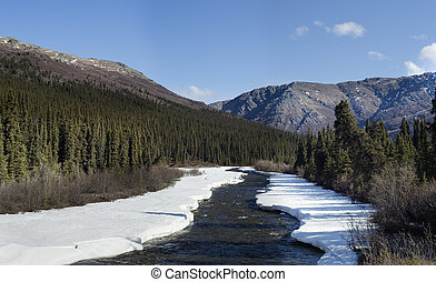 Unfreezing river in mountain country - Composite image, made...
