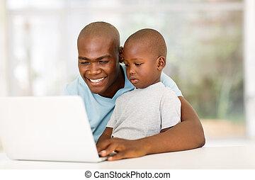 ung, afrikan bemanna, användande laptop, med, hans, son