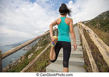 ung, fitness, kvinna, gångmatta, sträckande, ben, på, fjäll, skugga
