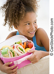 ung flicka, holdingen, packad lunch, in, vardagsrum, le