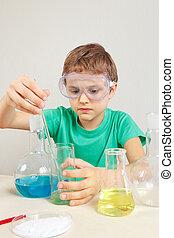 ung, forskare, in, säkerhetsgoggles, gör, kemisk, prov, in, laboratorium