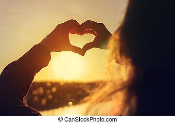 ung kvinde, indgåelse, hjerte, hos, hende, hænder, hos, solnedgang
