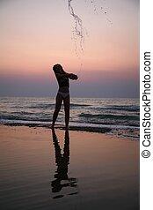 ung kvinde, sprinkles, af, vand, på, strand, på, solnedgang