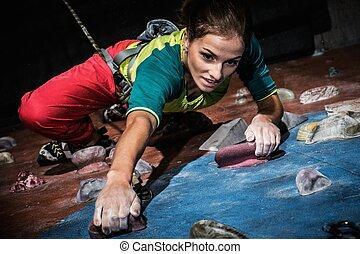 ung kvinna, öva, bergbestigning, på, a, rock vägg, inomhus