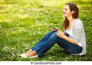 ung kvinna, användande, henne, kompress, dator, medan, avkopplande, utomhus
