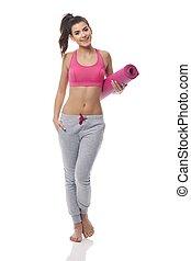 ung kvinna, bärande, yoga matta