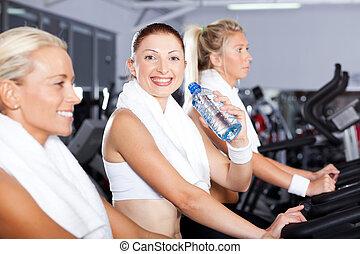 ung kvinna, dricksvatten, in, gymnastiksal