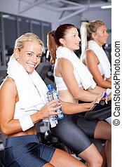ung kvinna, dricksvatten, medan, cykling, in, gymnastiksal