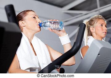 ung kvinna, dricksvatten, medan, exercerande, in, gymnastiksal