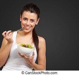 ung kvinna, holdingen, och, äta, sallad