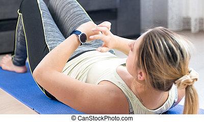 ung kvinna, lögnaktig, på, fitness, matta, och, användande, fitness, smart, uren