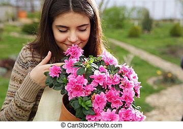 ung kvinna, lukta, rosa blommar, in, trädgård