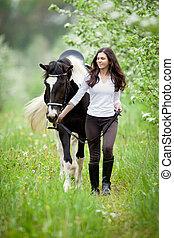 ung kvinna, och, pinto, häst, in, äpple, garden., häst, och, vacker, dam, vandrande, outdoor.