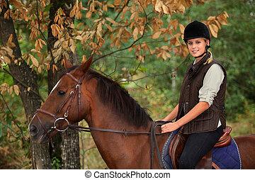 ung kvinna, ridande, a, häst, genom, skogig