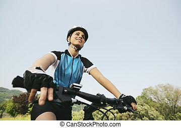 ung kvinna, utbildning, på, fjäll cykel, och, cykling, i park