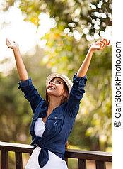 ung kvinna, utomhus, med, beväpnar outstretched
